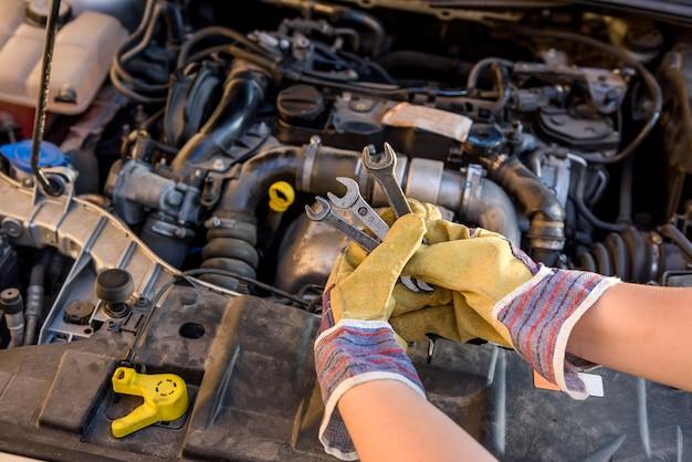 Ręce w rękawicach ochronnych z kluczami przeciw silnikowi samochodowemu