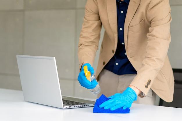 Ręce w rękawiczkach do czyszczenia biurka
