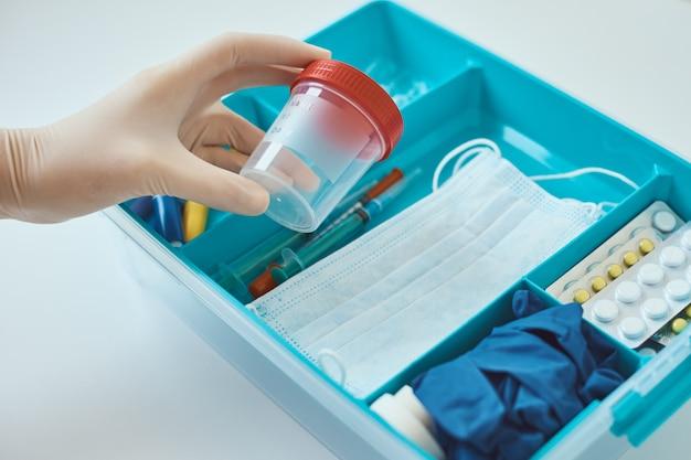 Ręce w rękawiczkach medycznych wyjmują kubek testowy z apteczki. pojęcie opieki zdrowotnej i medycyny. apteczka