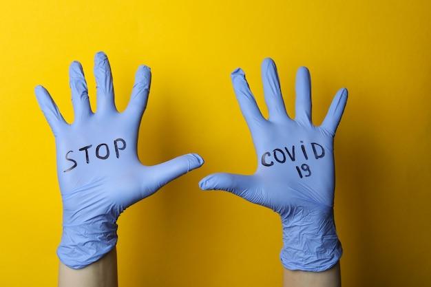 Ręce w rękawiczkach medycznych z tekstem stop covid-19 na żółtym tle na białym tle