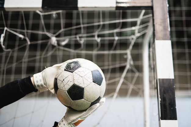 Ręce w rękawiczkach odnoszącego sukcesy bramkarza złapały piłkę nożną o siatkę w bramie podczas meczu piłki nożnej
