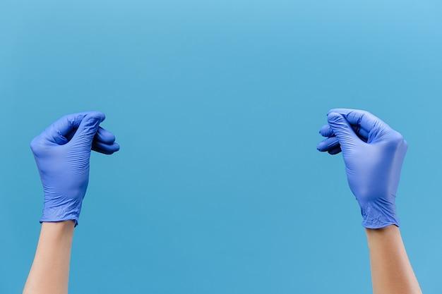 Ręce w rękawiczkach pocierają palce pokazujące gest gotówki