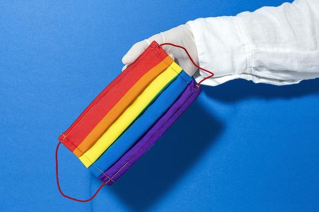 Ręce w rękawiczkach przedstawiające domową modę i projektowe maski lgbt do ochrony przed covid-19