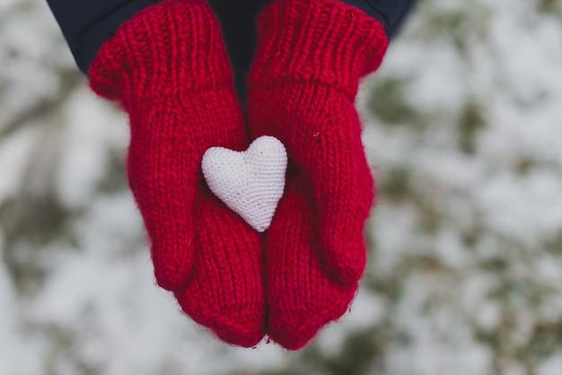 Ręce w rękawiczkach trzyma białą serce