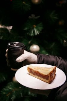 Ręce w rękawiczkach trzymają filiżankę gorącej kawy i kawałek ciasta. kawa na zimę