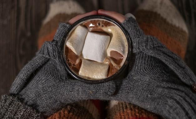 Ręce w rękawiczkach trzymają pianki w starym kubku retro z białego żelaza