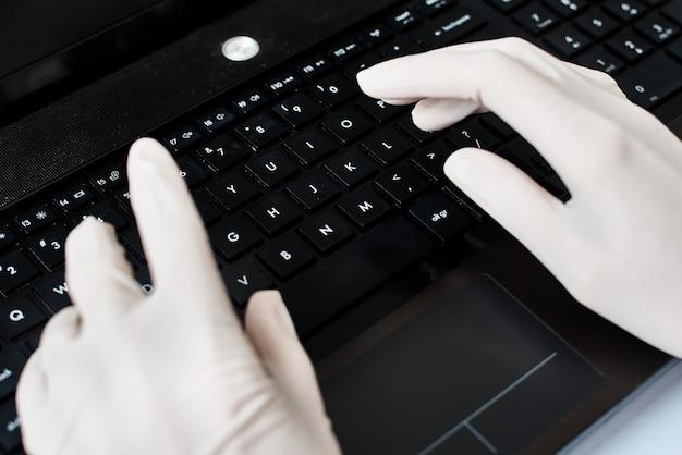 Ręce w rękawiczkach, wpisując na klawiaturze laptopa. koncepcja ochrony przed wirusami