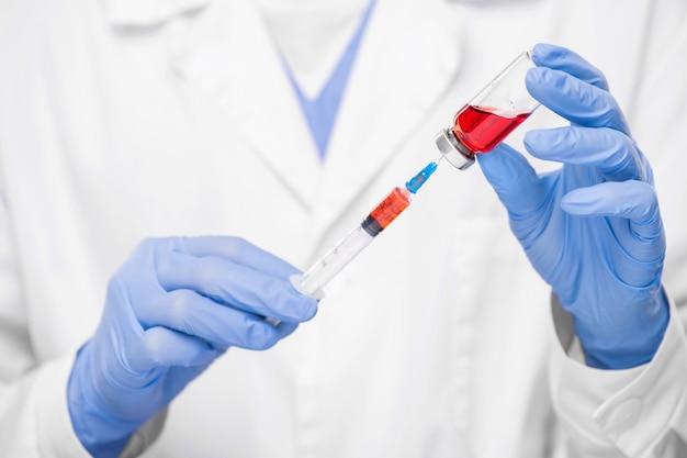 Ręce w rękawiczkach współczesnego wirusologa lub pielęgniarki biorącego płynną szczepionkę do strzykawki podczas wykonywania zastrzyku pacjentowi z covid19