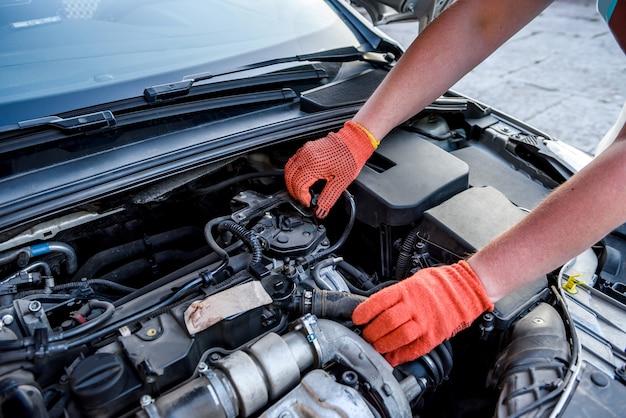 Ręce w rękawiczkach z silnikiem samochodowym z bliska
