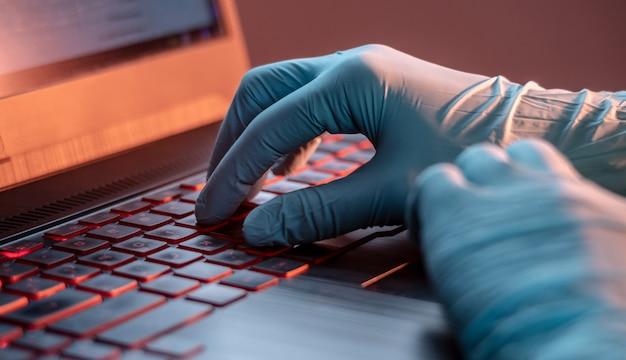 Ręce w rękawiczki medyczne wpisz na klawiaturze laptopa w zbliżenie
