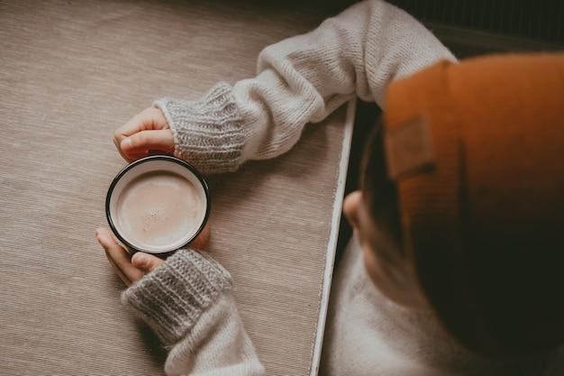 Ręce w swetrze trzymają gorące kakao, w czerwonym kubku, widok z góry. przytulne zdjęcie z kubkiem w ręku z miejscem na kopię. dziecko pije gorącą czekoladę