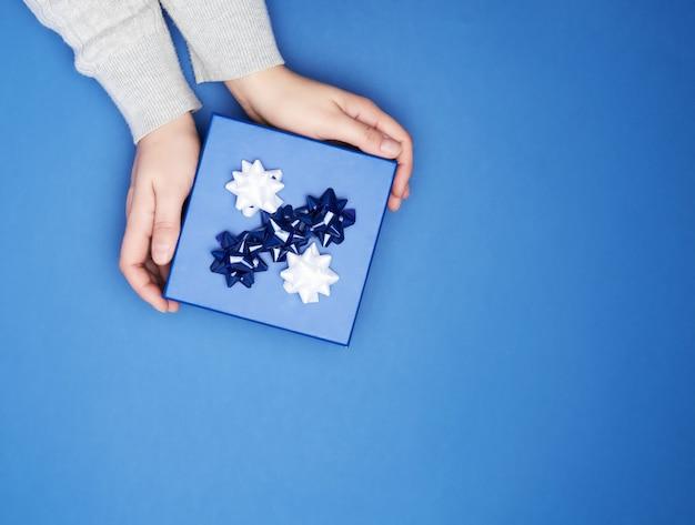Ręce w szarym swetrze trzymają zamknięte kwadratowe niebieskie pudełko z kokardą