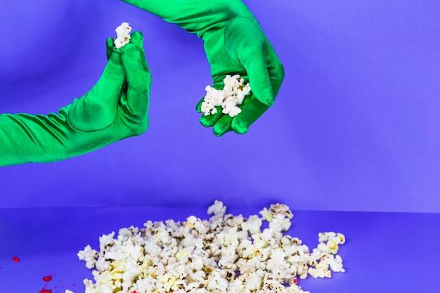 Ręce w zielone rękawiczki gospodarstwa popcorn