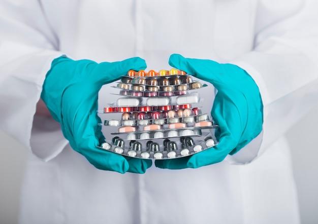 Ręce w zielonych rękawiczkach lateksowych, trzymając stos różnych tabletek, antybiotyków i tabletek do leczenia wirusów na szarej ścianie szpitala.