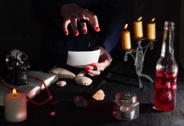 Ręce wiedźmy nad fotograficznym rytuałem magicznym i akcesoriami