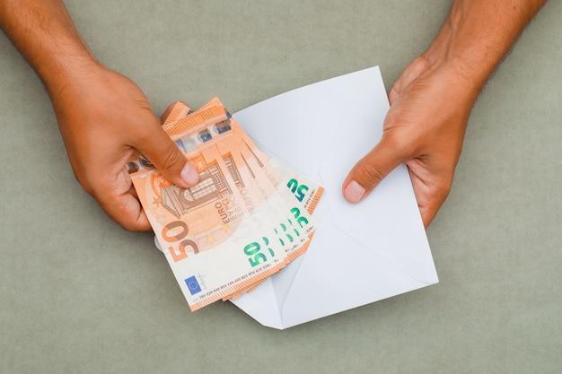 Ręce wkładanie banknotów do koperty.