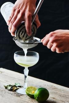 Ręce wlewają przez sito do szklanego koktajlu daiquiri na drewnianym stole na czarnym tle