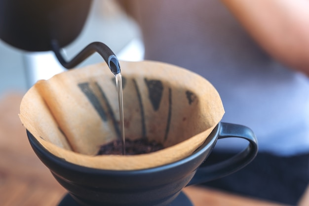Ręce wlewając gorącą wodę, aby zrobić kroplówkę kawy na vintage drewnianym stole