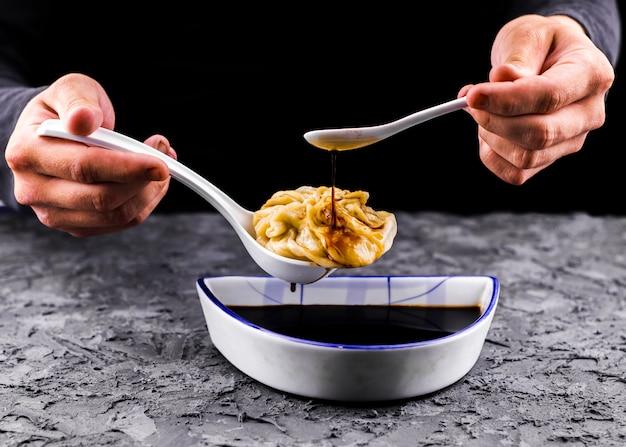 Ręce wlewając sos na widok z przodu kluski