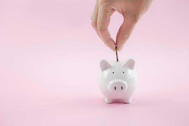 Ręce włożyły monetę do skarbonki na różowym tle, aby zaoszczędzić bogactwo pieniędzy