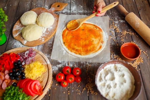 Ręce womanb nakładanie sosu na ciasto podczas gotowania