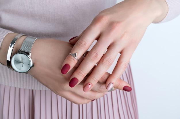 Ręce womans ze srebrną biżuterią i akcesoriami. dziewczyna z minimalistycznym wzorem różowego wiosennego lata manicure.