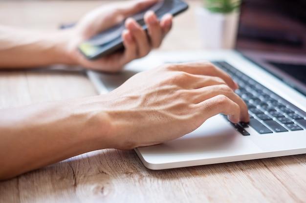Ręce, wpisując na klawiaturze laptopa