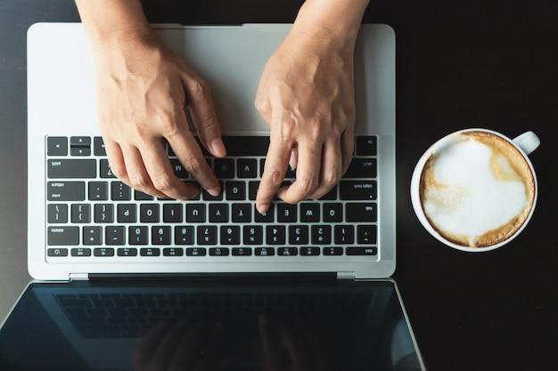 Ręce wpisując przycisk na laptopie na czarny drewniany stół