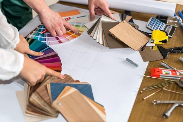 Ręce wskazujące na próbki kolorów do renowacji, zbliżenie