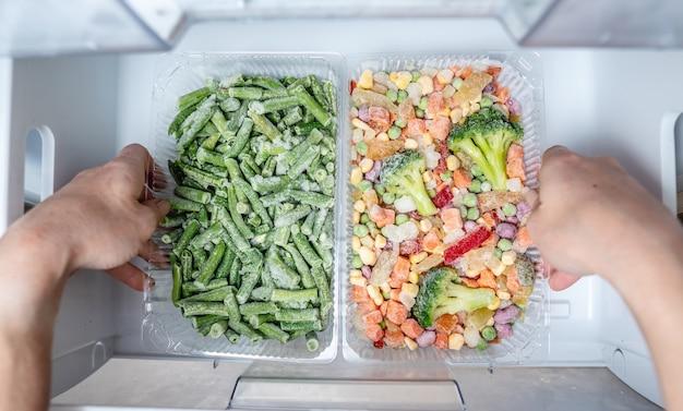 Ręce wyciągają pojemnik z zamrożonymi warzywami z zamrażarki lodówki