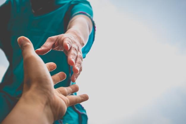 Ręce wyciągają ręce, aby sobie pomóc