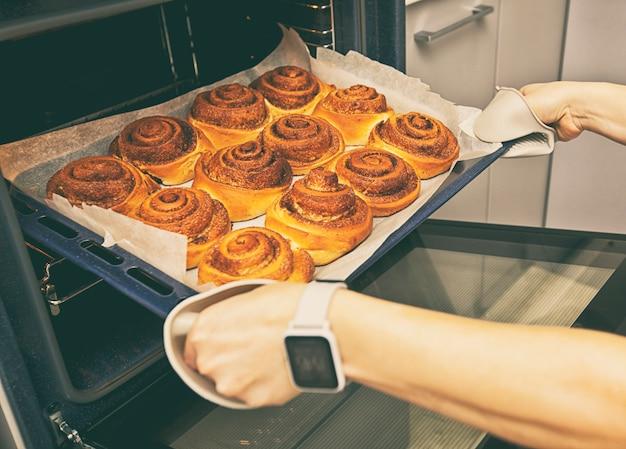 Ręce wyciągające świeżą piekarnię z pieca