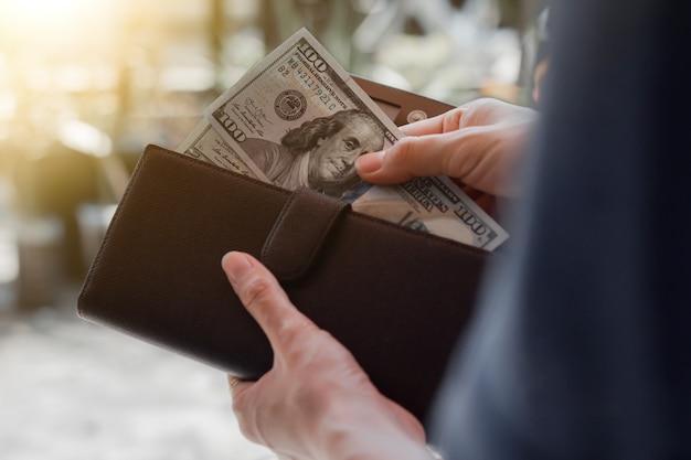 Ręce wyjmują nam banknoty dolarowe z brązowego skórzanego portfela