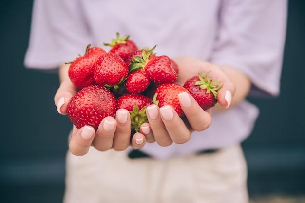 Ręce younwoman trzymające czerwone truskawki i wiśnie