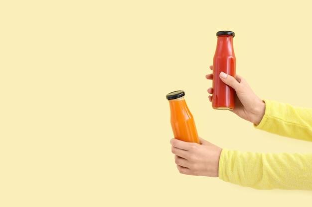 Ręce z butelkami zdrowego smoothie na kolorowej powierzchni