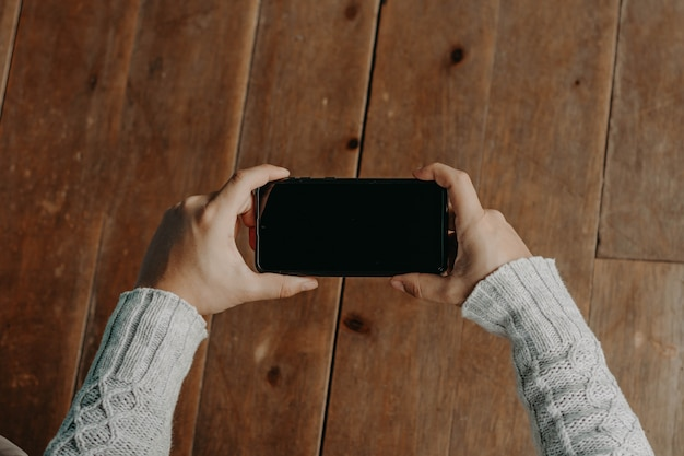 Ręce z czarnym telefonem. inteligentny telefon