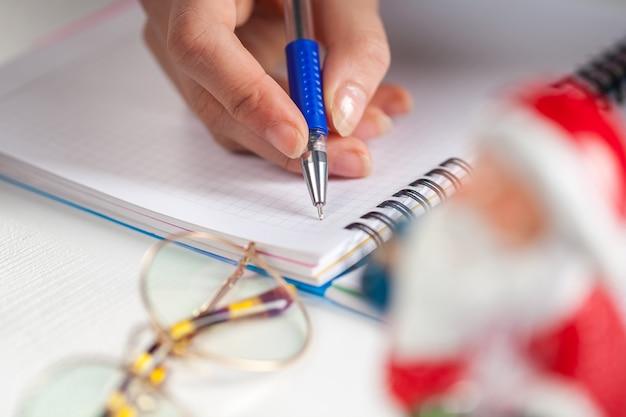 Ręce z długopisem, notatnikiem i kopertą na list