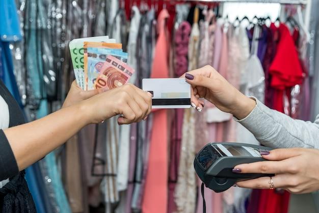 Ręce z euro i kartą kredytową płacą za zakup