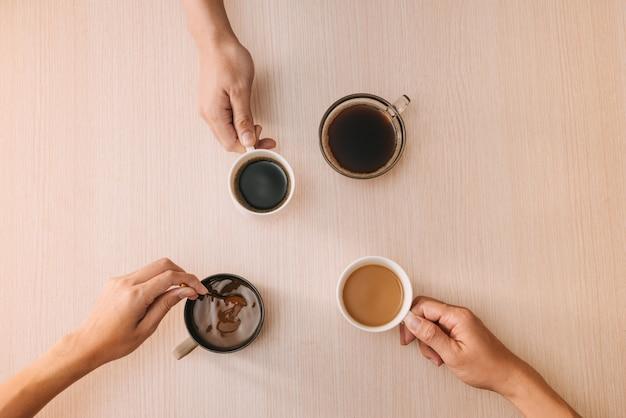 Ręce z filiżankami kawy na powierzchni drewna