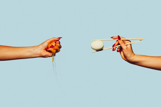Ręce z jajkami. kolaż sztuki współczesnej w stylu pop-art. ręce na białym tle na modnym kolorowym tle z copyspace, kontrast. nowoczesny design z copyspace na reklamę. modne kolory.