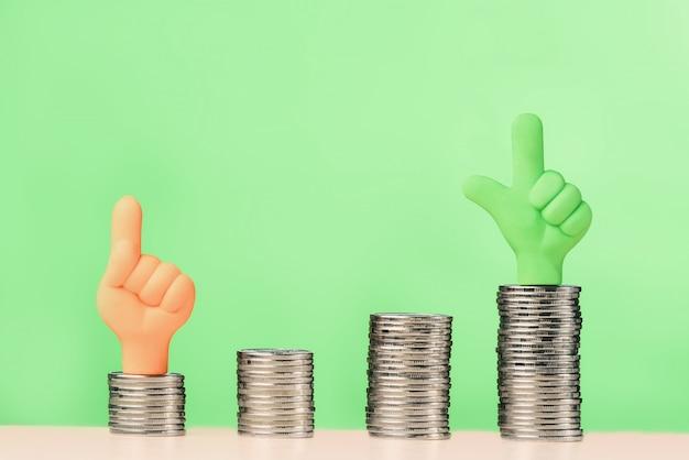 Ręce z kciuki do góry na stosy monet. koncepcja wzrostu inwestycji.