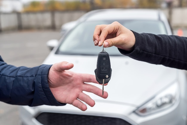 Ręce z kluczami przed nowym samochodem z bliska