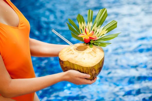 Ręce z kokosem na tle basenu