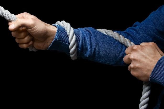 Ręce z liną na czarnej ścianie
