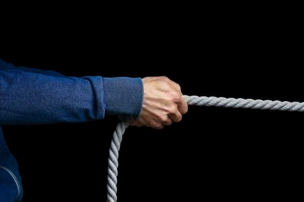 Ręce z liną na czarnym tle. mężczyzna ciągnie walkę na linie.