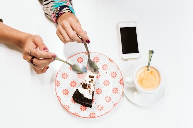 Ręce z łyżkami dzielące kawałek ciasta