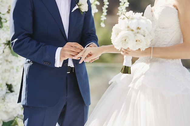 Ręce z obrączki. modny pan młody nakłada złoty palec na palec panny młodej podczas ceremonii ślubnej. kochająca para, kobieta w sukni ślubnej i przystojny mężczyzna w stylowym niebieskim garniturze