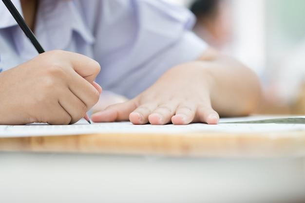 Ręce z ołówkiem na formularzu zgłoszeniowym, studenci biorący udział w egzaminach, piszący pokój egzaminacyjny