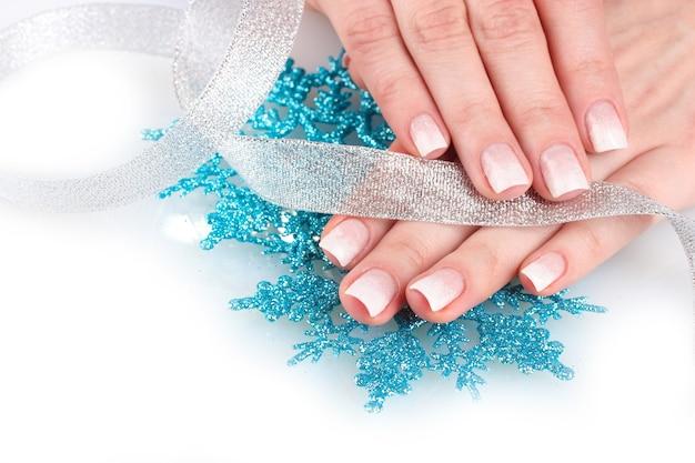 Ręce z pięknym zimowym wzorem, płatkami śniegu i wstążką na białej powierzchni