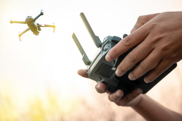 Ręce z pilotem zdalnego sterowania dronem na zewnątrz.